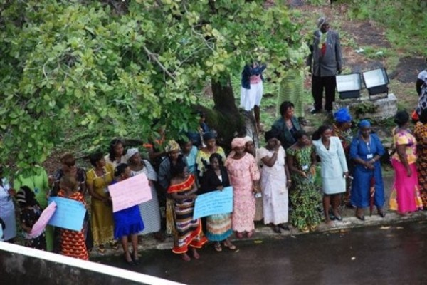 Liberian women line the road to wait to greet Secretary Clinton's motorcade, Aug. 13, 2009(AP Photo/Pewee Flomoku)