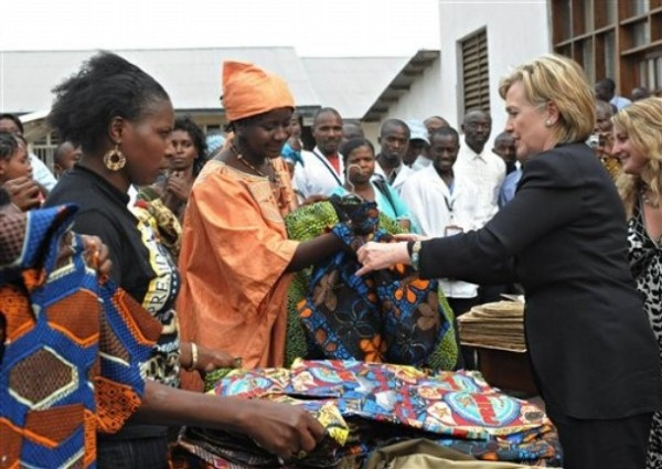 US Secretary of State Hillary Rodham Clinton, right, purchases a shirt , at the Heal Africa clinic in Goma, Congo Tuesday Aug. 11, 2009.  (AP Photo/Roberto Schmidt, Pool)