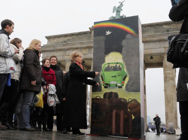 Secretary of State Hillary Clinton (L, next to a segment of the Berlin Wall) poses with a group of pupils in front of Brandenburg Gate in Berlin, Germany, 09 November 2009. Clinton is Berlin for the official celebrations marking the 20th anniversary of the fall of the Berlin Wall. Some 1.000 segments of the Berlin Wall, cut into domino shape and painted by different groups of people, have been put up to form a 1,5km long array of dominos alongside the former course of the Berlin Wall between the Reichstag building, Brandenburg Gate and Potsdam Square. On the evening of the 09 November 2009 the fall of the dominos will symbollically reenact the fall of the wall 20 years ago.  EPA/RAINER JENSEN
