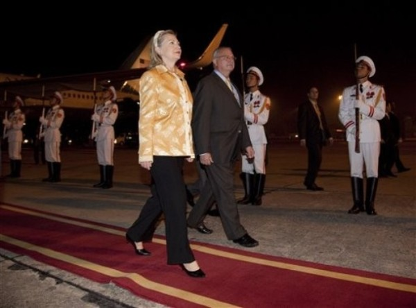 Secretary of State Hillary Rodham Clinton, left, and U.S. Ambassador to Vietnam Michael Michalak walk past an honor guard after arriving at No Bi International airport for the 17th ASEAN Summit on Friday, Oct. 29, 2010 in Hanoi, Vietnam.   (AP Photo/Evan Vucci, Pool)